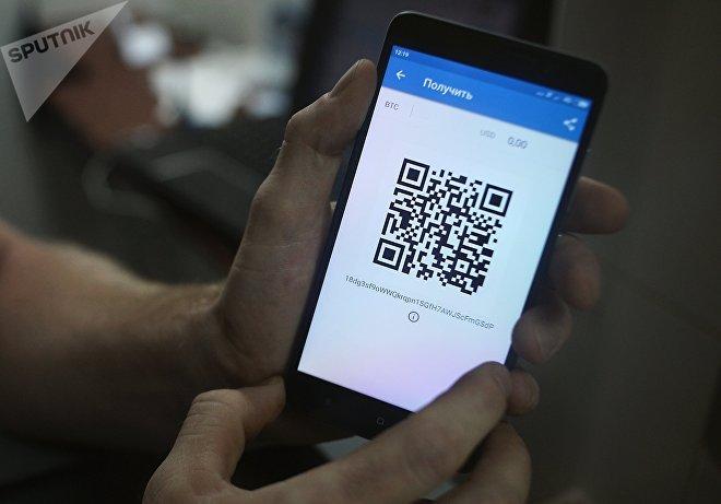 Демонстрация на смартфоне мобильного приложения для работы с криптовалютой биткоин в стационарном обменном пункте криптовалют в Москве