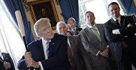 Президент США Дональд Трамп размахивает бейсбольной битой во время демонстрации продукта «Сделано в Америке» в Белом доме в Вашингтоне