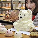 Продавец показывает рождественские торты в торговом центре Токио
