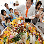 Повар нарезает 100-килограммовый торт-мороженое, украшенный фруктами, во время летнего фестиваля в Йокогаме, Япония