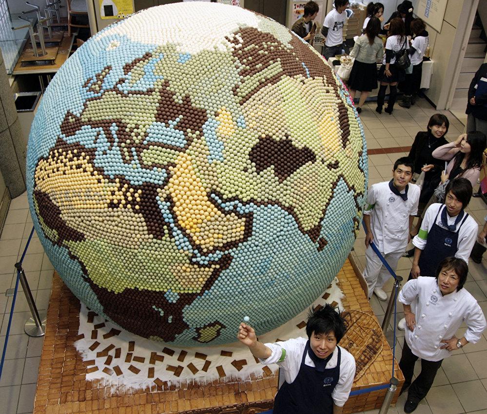Профессор и студенты кафедры кондитерской промышленности колледжа Отемае представляют шоколадный торт весом 800 кг, выполненный в виде планеты Земля, на фестивале в Осаке