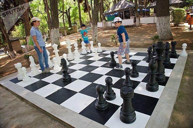 Дети играют фигурами на гигантской шахматной доске у тбилисского Дворца шахмат