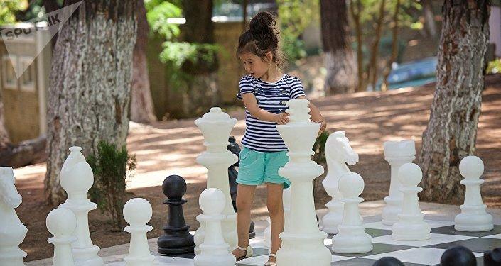 Девочка играет большими шахматными фигурами в парке у тбилисского Дворца шахмат