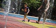 Мальчик с мамой бегают под струями фонтана в одном из тбилисских парков жарким летним днем