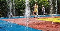 Дети бегают под струями фонтана в одном из тбилисских парков жарким летним днем