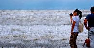 Туристы на пляже в Батуми смотрят на море