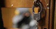 Наручники на двери клети для скамьи подсудимых в зале суда
