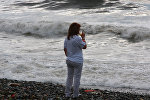 Турист фотографирует волны в момент волнения на Черном море