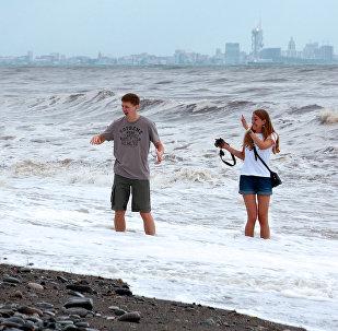 Туристы фотографируются в море на набережной Батуми
