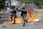 Сотрудник сил безопасности на митинге во время забастовки против правительства президента Венесуэлы Николаса Мадуро в Каракасе, Венесуэла