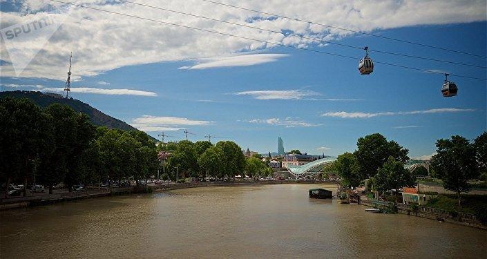 Кабинки канатной дороги над рекой Кура в центре Тбилиси