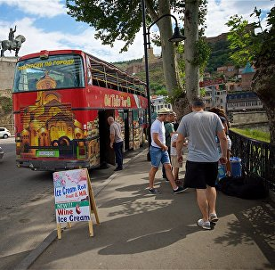Туристы в историческом центре Тбилиси и прогулочный автобус