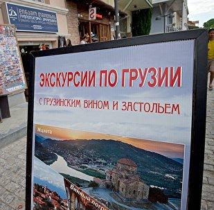 Туризм в Грузии - туристический баннер с объявлением о турах по стране в историческом центре Тбилиси