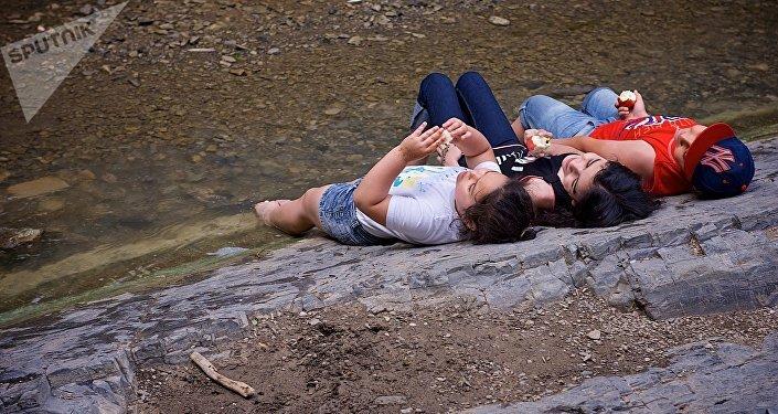 Люди лежат в прохладной тени на каменистом берегу у воды в тбилисском Ботаническом саду, отдыхая от летней жары