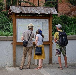 ტურისტები საინფორმაციო სტენდთან თბილისში
