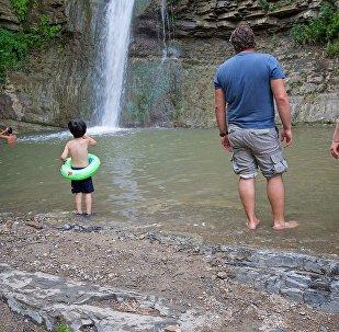Семейство отдыхает в летнюю жару у водопада в тбилисском Ботаническом саду