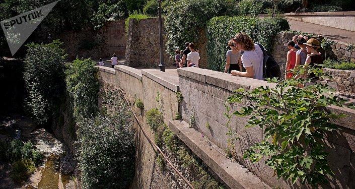 Туристы идут по центральной аллее тбилисского Ботанического сада, с которой открывается вид на реку Цавкисисцкали