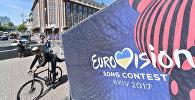 Человек едет на велосипеде мимо официального логотипа конкурса песни «Евровидение» в центре Киева
