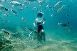 Женщина ныряет и делает вид, что катается на велосипеде, в Подводном парке в Пуле, Хорватия