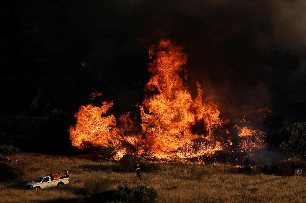 Пожарная служба Греции сообщила, что 15 августа на острове Самос было найдено самодельное устройство для поджога, сделанное на основе аэрозольного баллона. Источники в пожарной службе заявляли Афинскому агентству новостей, что, по их мнению, поджоги являются спланированными, однако официальные представители правительства избегают говорить о преднамеренных поджогах, говоря, что прежде необходимо провести расследование. На фото - пожарный на фоне пламени во время лесного пожара в районе Калывии, вблизи Афин, Греция