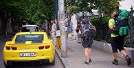 Туристы с рюкзаками идут по одной из тбилисских улиц
