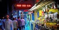 Туристы идут мимо обменного пункта и сувенирной лавки в центре грузинской столицы