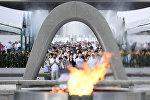 Люди молятся за жертв атомной бомбы в мемориальном парке в Хиросиме, Япония