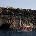 Туристы проплывают под сторожевой башней Санта-Мария 17 века на Комино, самом маленьком из трех обитаемых островов, которые составляют Мальтийский архипелаг. Между Комино и маленьким близлежащим островком Коминотто располагается Голубая лагуна с прозрачной голубой водой. Эта живописная бухта с белым песком на дне и большим количеством морских обитателей постоянно притягивает большое количество туристов