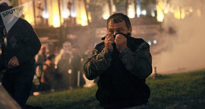 Участник акции протеста грузинской оппозиции закрывает лицо от слезоточивого газа во время беспорядков на проспекте Руставели в Тбилиси, 2011 год