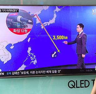 Южнокорейский солдат проходит мимо телевизионного экрана, где демонстрируется график расстояния между Северной Кореей и Гуамом, на железнодорожной станции в Сеуле