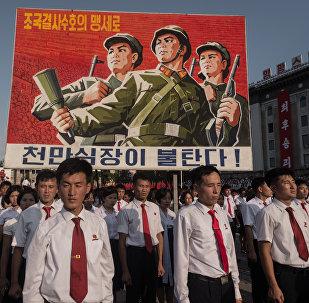 Люди несут плакат во время митинга в поддержку позиции Северной Кореи против США на площади Ким Ир Сена в Пхеньяне