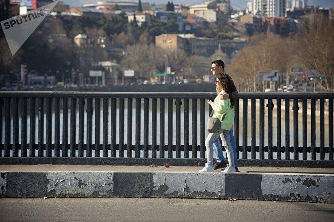 Молодые люди идут по тбилисской набережной