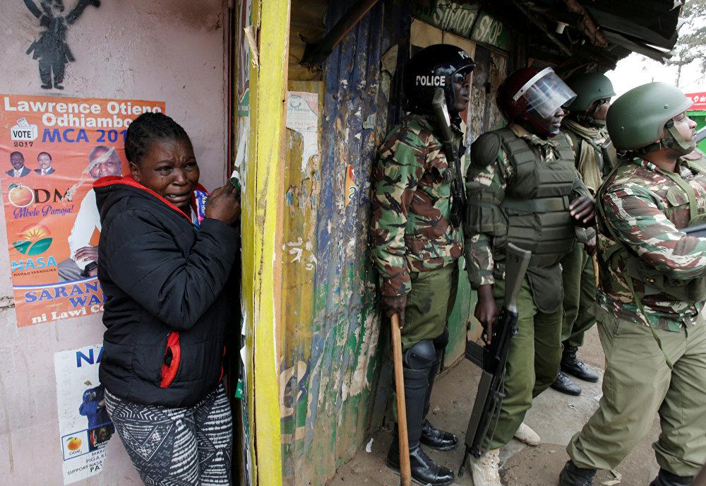 Массовые беспорядки начались в нескольких кенийских городах после оглашения результатов президентских выборов. На фото - женщина плачет, стоя за полицейскими, во время столкновений между сторонником лидера оппозиции Раилы Одгинга и полицейскими в трущобах Киберы в Найроби