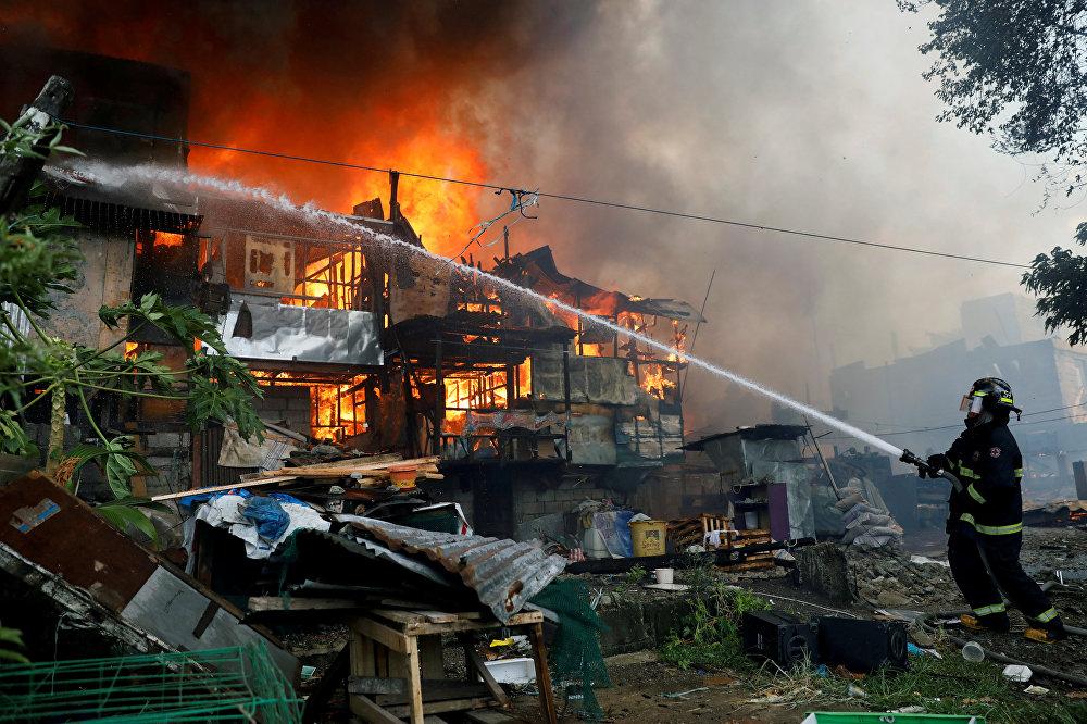 Пожарный тушит на лачуги, охваченные пламенем во время пожара в жилом районе Кесон-Сити, Филиппины