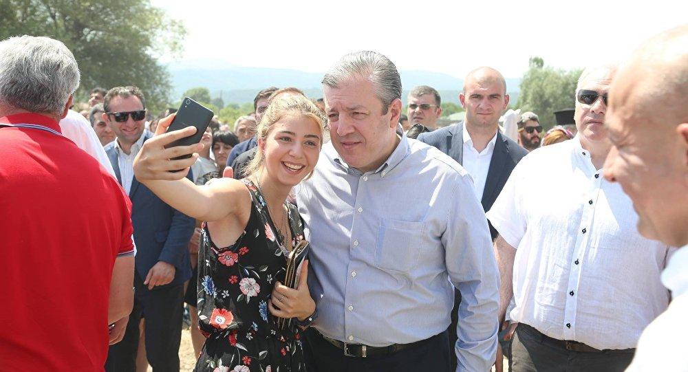 Девушка фотографируется с премьером Грузии Георгием Квирикашвили