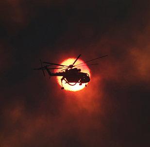 სახანძრო ვერტმფრენი ჩამავალი მზის ფონზე სოფელი კაპანდრიტის მახლობლად ხანძრის ჩაქრობის დროს, საბერძნეთი