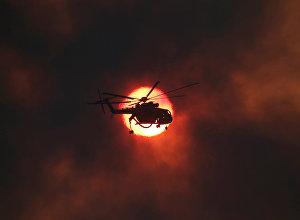 Пожарный вертолет на фоне заходящего солнца во время тушения лесного пожара около деревни Капандрити, к северу от Афин, Греция
