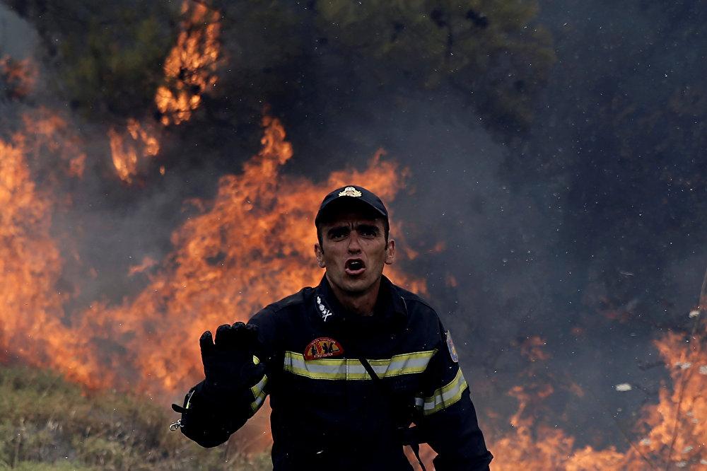 В 2007 году по всей Греции также полыхали пожары. Многие обозреватели уверены, что их причиной были поджоги с целью дестабилизировать ситуацию в стране и отстранить от власти бывшего премьер-министра Костаса Караманлиса. На фото - пожарный у деревни Капандрити, к северу от Афин, Греция