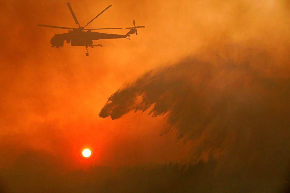 В связи с большим распространением и интенсивностью пожаров и учитывая, что в ближайшие дни будет высокий риск, наша страна подала запрос через Европейский механизм гражданской защиты IRCC на международную помощь в воздушных силах (для тушения пожаров), конкретно — на две пары самолетов CL-415, — сообщила пожарная служба Греции. На фото - пожарный вертолет сбрасывает воду на лесной пожар у деревни Меточи