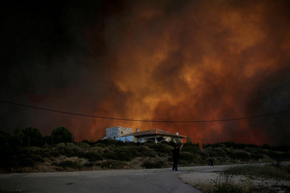 Кипр сообщил, что отправит группу пожарных из 60 человек. Франция, которая имеет пожарные самолеты, отказала в помощи из-за многочисленных пожаров у себя. На фото - черный дым поднимается позади дома во время лесного пожара около деревни Варнавас