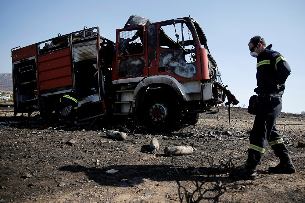 Лесные пожары распространяются так быстро, что спастись от них порой не успевают даже сами пожарные. На фото - сгоревшая пожарная машина в Каливии