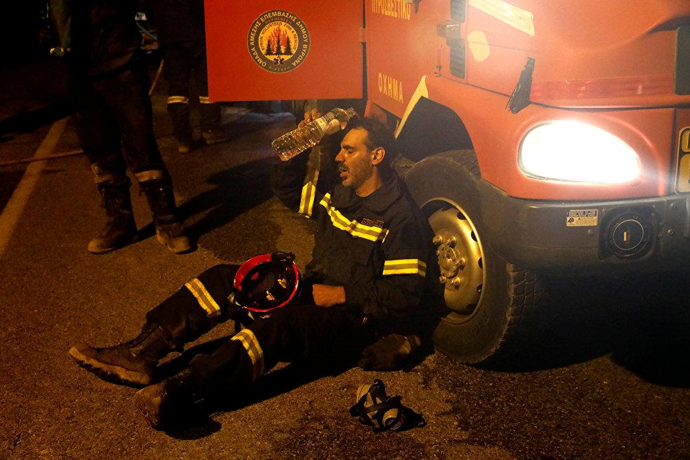 С начала августа по всей Греции полыхают лесные пожары, у пожарных не хватает сил на их ликвидацию. На фото - пожарный поливает голову водой во время отдыха после тушения пожара у деревни Меточи