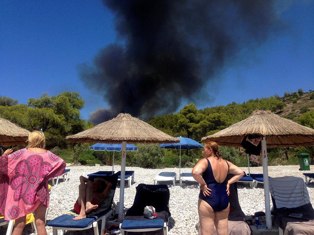 Только за последние дни в Греции зафиксированы десятки новых пожаров. 14 августа появился 91 новый лесной пожар, 15 августа — 55 очагов. За последние сутки были отмечены 33 новых лесных пожара. На фото - туристы смотрят на дым от лесного пожара на острове Спецес