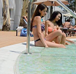 Отдыхающие летом загорают у бассейна в Батуми
