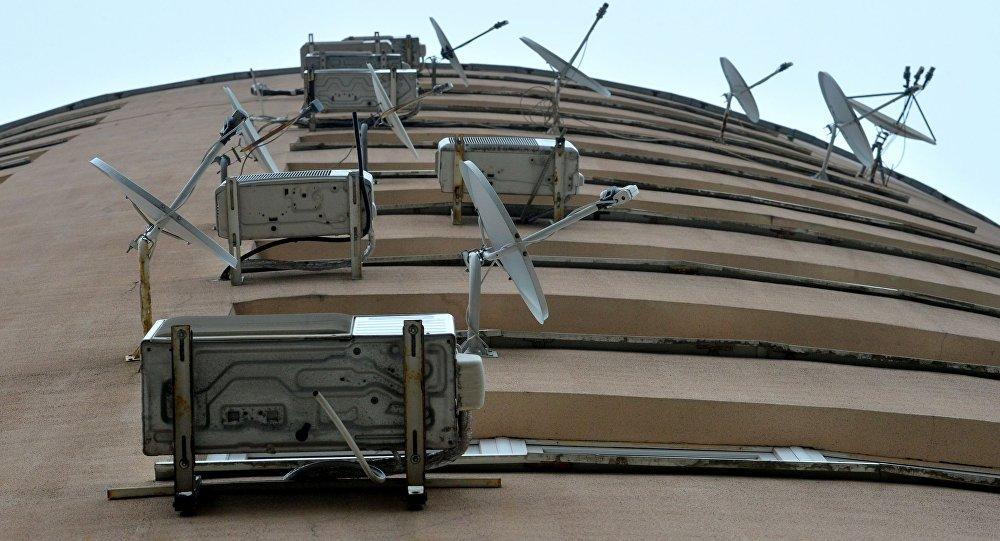 Кондиционеры и спутниковые тарелки на фасаде здания