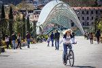 Девушка катается на велосипеде у Моста мира