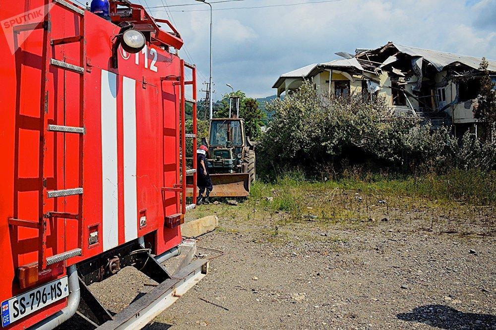 Пожарные на месте взрыва на фоне разрушенного дома у газозаправочной станции