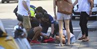 Люди помогают пострадавшим после наезда на прохожих в Барселоне