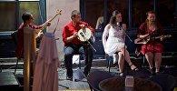 Музыканты в летнем ресторане поют под открытым небом