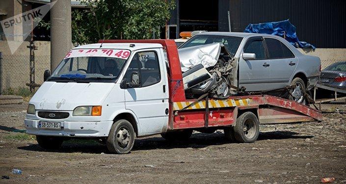 Эвакуатор с разбитой машиной на авторазборке